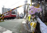 男性2人が電車にはねられ死亡した踏切のそばに手向けられた花=川崎市川崎区で2017年4月17日午前7時54分、竹内紀臣撮影