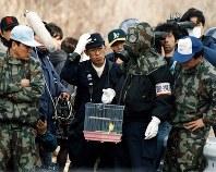 教団施設でガスマスクをかぶり毒ガス検知用のカナリアの鳥かごを準備する警視庁捜査員=山梨県で1995年3月31日