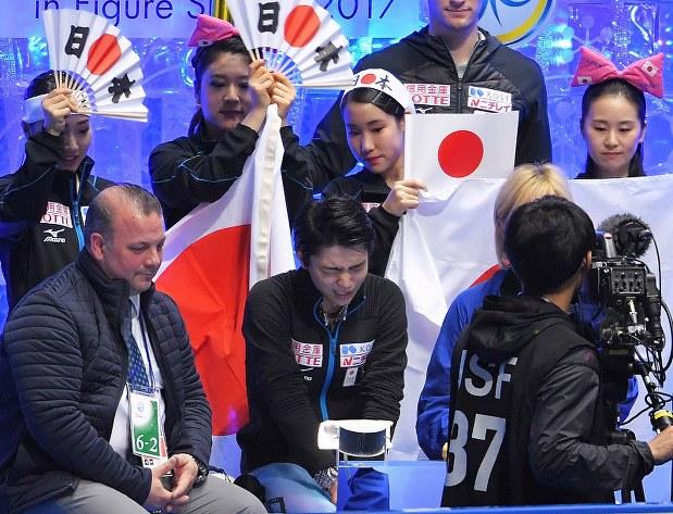 男子シングル・ショートプログラムを終え、日本チームのメンバーに囲まれる中、険しい表情を見せる羽生結弦(中央)=東京・代々木競技場2017年4月20日、手塚耕一郎撮影