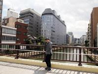 霊岸橋を渡る春風亭一之輔さん。お花と半七もこの橋を走って、霊岸島(左手)のおじさんの家に行ったのだろうか=東京都中央区で