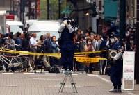 現金が奪われた現場付近を調べる警視庁の捜査員ら=東京都中央区で2017年4月21日午後3時16分、小川昌宏撮影