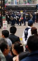 大勢の観光客らが見つめる中、現金が奪われた現場付近を調べる警視庁の捜査員ら=東京都中央区で2017年4月21日午後3時33分、小川昌宏撮影