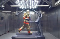 A firefighter runs on a treadmill under lighting that mimics sunlight in the Tokyo Fire Department's Fire Technology and Safety Laboratory's test room in Shibuya Ward on April 20, 2017. (Mainichi)