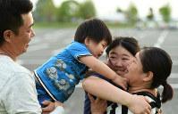 車中泊を1カ月ほど続けた駐車場を訪れた(左から)大山祐介さん、裕己ちゃん、愛歩さん、るみさん。祐介さんは1年前、同じ場所でハイハイをしていた裕己ちゃんが駆け回る姿を見ながら「今思うとつらかった場所というより、ボランティアやいろいろな人たちと出会って人の温かさを実感できた場所」と話した=熊本県益城町で2017年4月16日、久保玲撮影