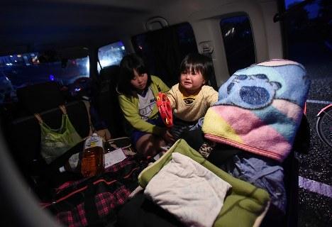 車中泊を続ける車内で大山愛歩さん(奥)と過ごす裕己ちゃん。周囲が暗くなると裕己ちゃんは不安で泣いてしまう=熊本県益城町で2016年4月20日、久保玲撮影