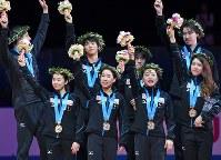 表彰式で、メダルを胸に笑顔で手を振る優勝した日本チームの選手たち=東京・国立代々木競技場で2017年4月22日、手塚耕一郎撮影