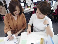 Cosmetics company employee Maki Kawaguchi, left, who has achieved workplace efficiency through taking inventory of her tasks, talks with her colleague on April 7, 2017, in Chuo Ward, Tokyo. (Mainichi)