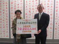 1万人目の入館者となった平澤優美子さん(左)と鎌田昌市館長=札幌市中央区の小原道城書道美術館で