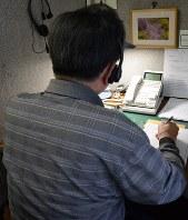 事務所の一室で電話を受ける相談員=札幌市内で
