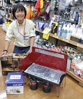 屋外用2口コンロ(右)や、風よけのついたカセットコンロ(左の箱)などのキャンプ用品売り場。初心者は専門店で注意点を聞くとよい=東京都千代田区の「さかいやスポーツ」で、大和田香織撮影