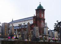 田平天主堂と墓地。墓石の上に十字架がある=長崎県平戸市で、八重樫裕一撮影