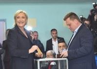 投票するマリーヌ・ルペン候補(左)=フランス北部エナンボーモンで2017年4月23日、八田浩輔撮影