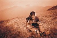 ミュージックビデオの撮影で訪れた朝霧高原での1枚。尾崎豊さんが足を投げ出してギターを演奏するショットは珍しいという=(C)山内順仁