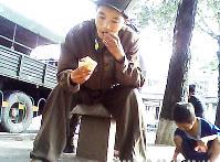 栄養失調で実家に戻される途中の兵士。見かねてパンを渡した。脇で少年がパンくずを拾っている=北朝鮮北部の町で2013年8月、取材協力者撮影