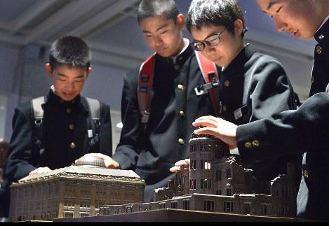 被爆前後の原爆ドーム(旧広島県産業奨励館)の模型を並べた展示コーナー「ふれるヒロシマ」で、原爆の威力を体感する生徒たち=広島市中区で2017年4月26日午前8時54分、山田尚弘撮影