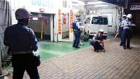 タワー型駐車場で、乗用車に歩行者がはねられた事故現場を調べる警察官=神戸市中央区で、原田悠自撮影