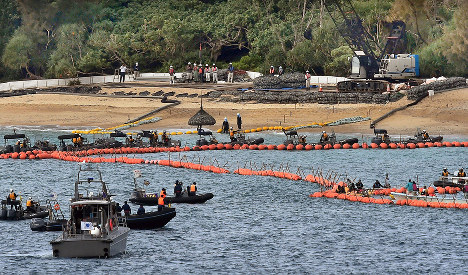 Rocks are lifted into a shallow area off the Henoko district of Nago, Okinawa Prefecture, following the commencement of shore protection work for the relocation of U.S. Marine Corps Air Station Futenma, on April 25, 2017. (Mainichi)