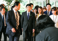 Reconstruction Minister Masahiro Imamura is surrounded by reporters after submitting his resignation, at the prime minister's office on April 26, 2017. (Mainichi)