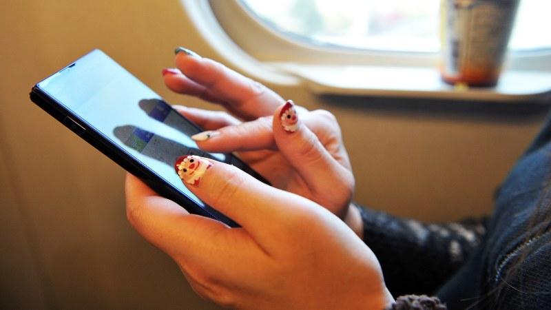 携帯電話のある風景=電車内で2015年12月6日、関口純撮影