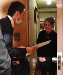 女性宅を訪問して特殊詐欺を防ぐための説明をする原宿署員(左)