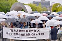 原爆慰霊碑前で核兵器廃絶と脱原発を訴える参加者=広島市中区で、山田尚弘撮影