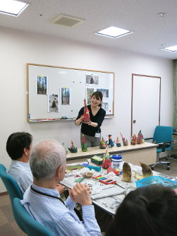 Clinical artist Kanako Obata, center, provides feedback on each work of art created by patients with early-onset dementia during a meeting of