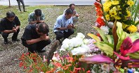 People pray for the soul of a 20-year-old woman at a site where her body was found in May last year, in this picture taken in the village of Onna, Okinawa Prefecture, on April 28, 2017. (Mainichi)