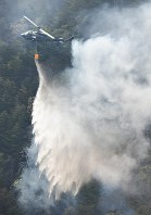 A Self-Defense Force helicopter discharges water over a state-owned mountain forest in Namie, Fukushima Prefecture, on the afternoon of April 30, 2017. (Mainichi)
