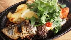 熱々の鉄板皿で提供される「丸ごと1匹!いわしの焼きポテトサラダ ポルトガル風」(880円税別、以下同)