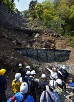 Reporters with special access look at a guard net that has been placed in a part of Kikuchi Gorge that was hit by a mudslide caused by the 2016 Kumamoto Earthquake, in the city of Kikuchi in Kumamoto Prefecture on May 1, 2017. (Mainichi)