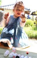 ワークショップで、フィルムケースや桃の種、数珠玉などをつかったマラカスづくりに挑戦する女の子=埼玉県東松山市で2017年5月5日、岡本同世撮影