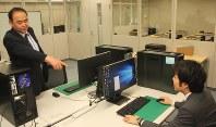 新設された「DFセンター」で、職員に指示する與那城一成・情報解析監理官(左)=千代田区の東京地検で