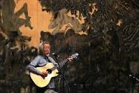 コンサートで、原爆投下の日が「今日でありつづける」という谷川俊太郎さんの詩に曲を付けた「その日」などを歌う小室等さん。会場から盛んな拍手がおくられ、涙ぐむ人もいた。背景は丸木夫妻の「アウシュビッツ」=埼玉県東松山市の「原爆の図丸木美術館」で2017年5月5日、岡本同世撮影