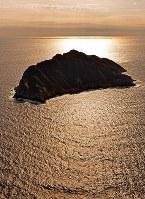 九州と朝鮮半島の間に位置する沖ノ島。約8万点の国宝が出土したことから「海の正倉院」とも呼ばれる=福岡県宗像市で2015年11月12日、本社ヘリから野田武撮影