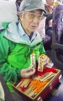 陸前高田に向かうバスの中で、カヌー仲間と手作りしたという木札を手にする小林勉さん。現地で知り合った人たちに渡す土産にするという