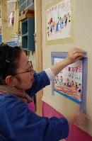 マスキングテープで壁に絵を貼り付ける佐藤さん=東京都練馬区の工房で、山崎明子撮影