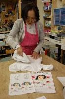 原画(手前右)を熱転写紙とアイロンでTシャツに写す作業をする吉田友子さん=東京都練馬区の工房で、山崎明子撮影