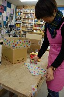 マスキングテープで段ボール箱を額に仕立てる山崎真希さん=東京都練馬区の工房で、山崎明子撮影