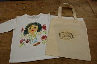 子どもの絵を写したTシャツ(左)とバッグ==東京都練馬区の工房で、山崎明子撮影