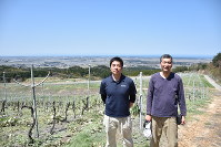 胎内市役所の坂上俊さん(左)と栽培責任者の佐藤彰彦さん=胎内市蔵王のブドウ畑で