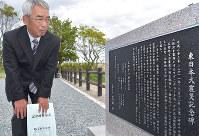 除幕された震災記念碑を眺める根本賢仁さん=広野町下浅見川で