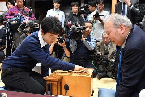 Fourth-dan shogi player Sota Fujii, left, reflects on his match with ninth-dan Hifumi Kato, right, after his professional debut at the Tokyo Shogi Hall on Dec. 24, 2016. (Mainichi)