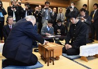 初手を指す加藤一二三九段(左)。右は藤井聡太四段=東京都渋谷区の将棋会館で2016年12月24日午前10時、猪飼健史撮影