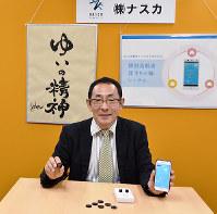 ビーコンと専用アプリを入れたスマホを手にする井上昌宏さん。「培ったICT技術で、街づくりを支援したい」と話す=滋賀県栗東市川辺で、土居和弘撮影