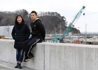 防潮堤に上った山本ヒデさん(左)と一慶さん。奥では新しい防潮堤の建設が進む=岩手県宮古市で、猪飼健史撮影
