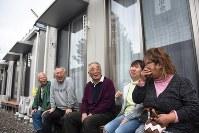 プレハブの縁側で住民と話し込む熊川勝さん(中央)。熊川さんの冗談で皆に笑みがこぼれた=福島県二本松市中ノ目の「塩沢農村広場仮設住宅」で4月26日