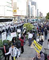 排外主義団体のデモ隊に歩道から抗議する市民たち=神戸市中央区で、栗田亨撮影