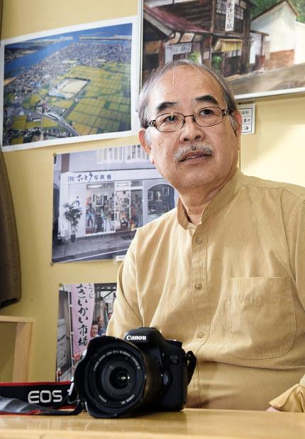 自身の写真館で思いを語る斎藤正善さん。震災前の写真館や空撮した閖上地区の写真が飾られている=宮城県名取市美田園7の「閖上さいかい市場」で
