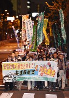 Demonstrators parade down a street in Tokyo's Chiyoda Ward after attending a major rally against the