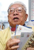 はがきを手に当時を振り返る西山進さん=福岡市南区で2017年5月9日、矢頭智剛撮影